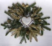 На венке ветвей ели и золотых хворостин и конусов лежит Ch Стоковое Фото