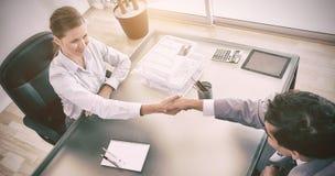 Над взглядом консультанта тряся руки с ее клиентом Стоковое Изображение