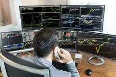 Над взглядом плеча биржевого маклера торгуя онлайн, говоря на мобильном телефоне Стоковые Изображения RF