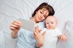 над взглядом Selfie Мама и ребенк с телефоном на b стоковые изображения rf