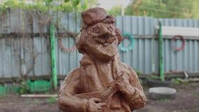 глиняная статуэтка мужчины с балалайкой clay figurine of a man with a balalaika stock video footage