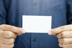 На визитные карточки владением руки человека людей показано пустую белую насмешку карты вверх стоковое изображение