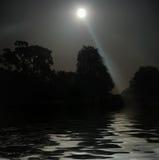 над водой полнолуния светя Стоковое Фото