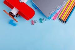 На голубой предпосылке тетради, зажимы, покрашенные карандаши, мел и красный самолет игрушки Взгляд сверху Стоковая Фотография RF