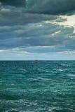 На горизонте моря далеко красная шлюпка Стоковые Изображения