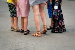 На горячий летний день, группа людей стоит на улице Только ноги видимые стоковые изображения rf