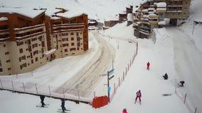 На день идти снег лыжники и snowboarders скользят вдоль моста скрещивания следа сток-видео