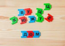 На деревянной лож предпосылки письма русского алфавита Ребенок клал вне надпись дома в русском Стоковые Изображения RF