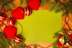 На деревянной поверхности ветвей спруса и игрушек рождества в форме сердца стоковое изображение