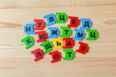 На деревянной предпосылке лежит группа в составе письма русского алфавита Стоковое Фото