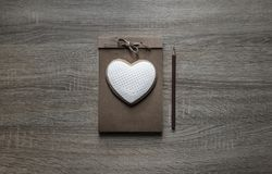 На деревянной предпосылке лежит notepaper ремесла scrapbooking на ем коричневый цвет карандаша сердца печенья Стоковое Изображение RF