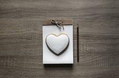 На деревянной предпосылке лежит notepaper ремесла scrapbooking на ем коричневый цвет карандаша сердца печенья Стоковая Фотография RF