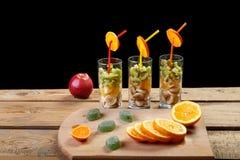 На деревянной предпосылке на разделочной доске части апельсина и мармелада рядом с стеклами в которых части frui Стоковые Фото