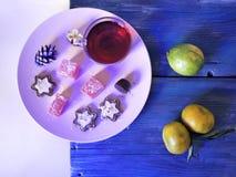 На деревянной текстурированной таблице розовое блюдо с помадками, оформление Нового Года, tangerines, чай стоковая фотография
