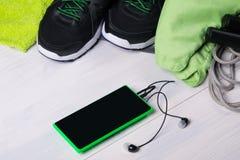 На деревянном поле комплект зеленых вещей для играть спорт, и телефоне Стоковая Фотография RF