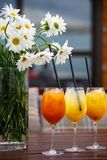 На деревянном столе коктейли плода и ваза цветков стоковая фотография rf