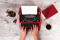 На деревянном столе машинка, рядом с которой канцелярские принадлежности и чашка кофе Стоковое фото RF
