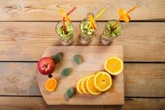 На деревянном столе на разделочной доске части апельсина, яблока и мармелада рядом с стеклами в которых части плодоовощ Стоковые Изображения RF