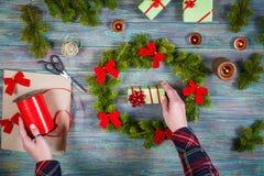 На деревянном столе, руки женщины делают крону на праздничный сезон стоковая фотография