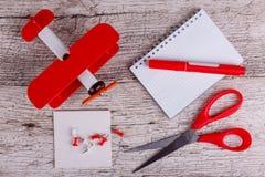 На деревянном столе самолет игрушки, тетрадь, бумага, отметка, струбцины и ножницы стоковые фото