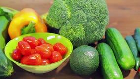 На деревянном столе свежие овощи цукини, брокколи, салат, авокадо, огурцы, перец и перец chili сток-видео