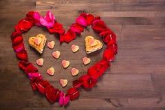 На деревянном столе сердце лепестков розы, внутри которых Стоковое Фото