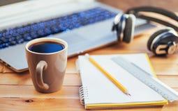 На деревянных карандаше, правителе и кофе тетради предпосылки компьтер-книжка наушников Стоковая Фотография