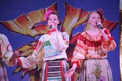 На девушках этапа красивых в национальных русских костюмах, sundresses мантий с живой вышивкой - группой люд-музыки колесо Стоковое фото RF
