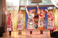 На девушках этапа красивых в национальных русских костюмах, sundresses мантий с живой вышивкой - группой люд-музыки колесо Стоковое Изображение RF