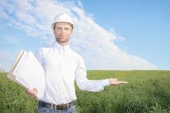 Надежный архитектор инженера построителя конструкции в белом шлеме держит в его чертежах руки жилого дома Стоковое Фото