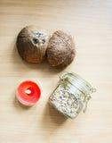 На деревянного стола стоимости отдельно красная свеча Таблетка ` вина ` с надписью Раздражайте с семенами льна на бежевом деревян Стоковые Изображения RF