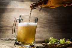 На деревянной предпосылке пиво пропускает от бутылки в кружке Стоковое Изображение