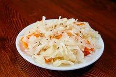 На деревянном столе белая плита с салатом замаринованной кабины Стоковая Фотография RF