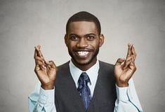 Надеющийся бизнесмен пересекая его пальцы стоковое изображение
