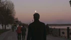 На заходе солнца, на сумраке, молодой человек в пальто идет вдоль тротуара вдоль реки задний взгляд видеоматериал