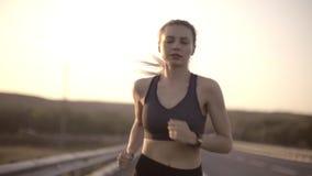 На заходе солнца шоссе бежит девушка спорт продолжает побежать несмотря на усталость сток-видео