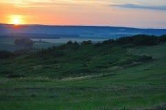 над заходом солнца поля Стоковые Изображения RF