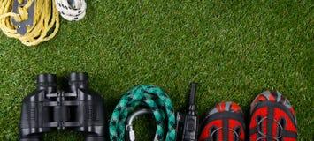 На зеленой лужайке ложь возражает быть поднятым к горам к высоте и замечанию природы, веревочки, штуцера, Стоковая Фотография