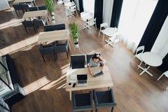 Надземная съемка женщины используя ее компьтер-книжку в кафе тротуара Взгляд сверху взрослой женщины сидя на таблице с чашкой Стоковое Фото