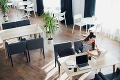 Надземная съемка молодой женщины сидя на таблице при чашка кофе и мобильный телефон занимаясь серфингом сеть на ее компьтер-книжк Стоковое Фото