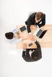 Надземные бизнесмены взгляда держа руки совместно на рабочем месте Стоковое Изображение