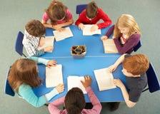 надземные ребенокы школьного возраста совместно осматривают работу Стоковое Изображение