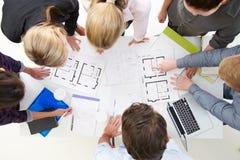 Надземный взгляд архитекторов обсуждая планы в офисе Стоковые Изображения RF