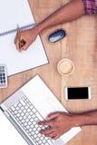 Надземный взгляд бизнесмена работая на компьтер-книжке пока пишущ на книге Стоковое Фото