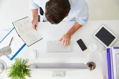 Надземный взгляд бизнесмена работая на компьютере в офисе Стоковое Изображение