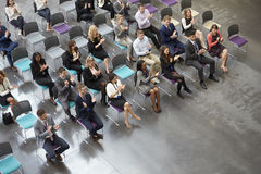 Надземный взгляд диктора аудитории аплодируя на конференции стоковое фото