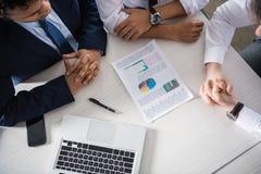 Надземный взгляд профессиональных бизнесменов обсуждая диаграммы на рабочем месте Стоковые Фотографии RF