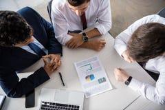 Надземный взгляд профессиональных бизнесменов обсуждая диаграммы на рабочем месте Стоковая Фотография