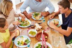 Надземный взгляд семьи сидя на таблице наслаждаясь едой Стоковое фото RF