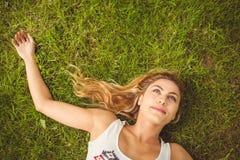 Надземный взгляд усмехаясь женщины лежа на траве Стоковое фото RF